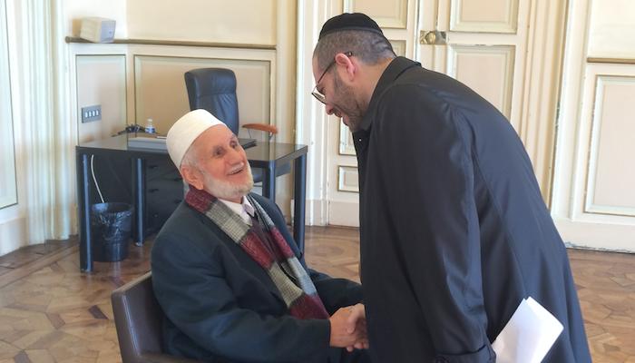 Lionel Dray saluant respectueusemment l'imam Bachir Dahmani et lui tenant la main.