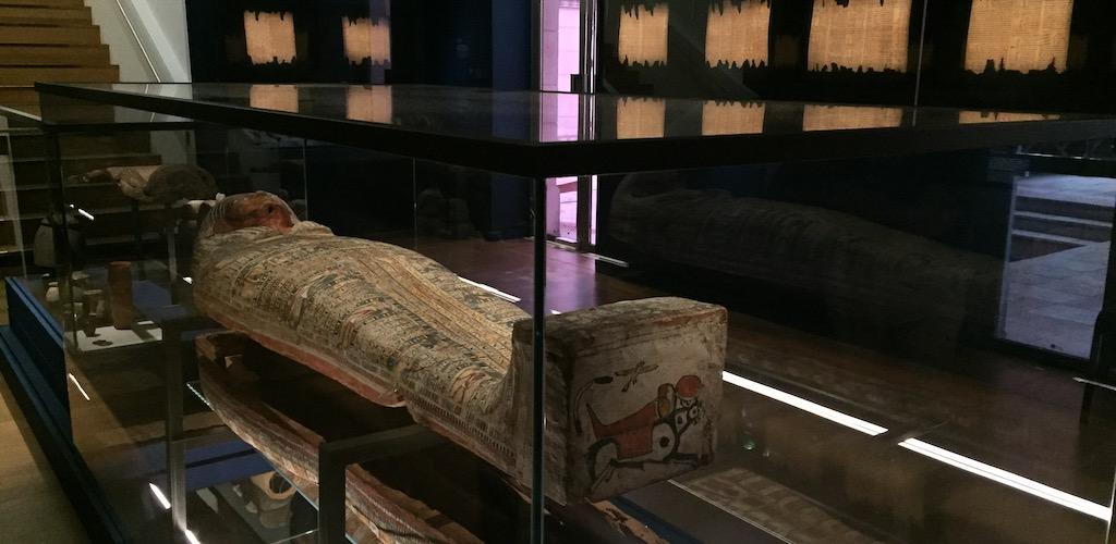 Salle d'exposition contenant un cercueil ouvert dans lequel on aperçoit une momie. Aux mur sont exposés les papyrus du Livre des morts.